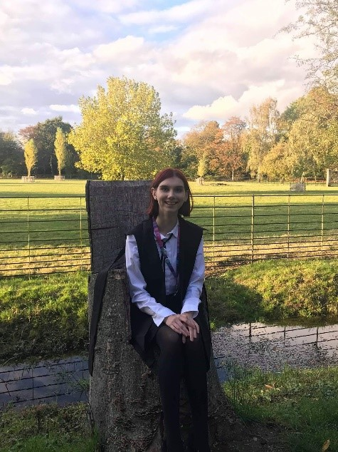 AJ (a red-haired girl) wearing subfusc and sitting on a tree-trunk chair after matriculation.