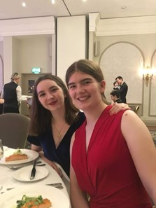 Annie (left) and Bethan (right) sat at a table with a white tablecloth in the Randolph hotel during the MedSoc Ball. A fillet of salmon is on Annie's plate. Both are smiling.