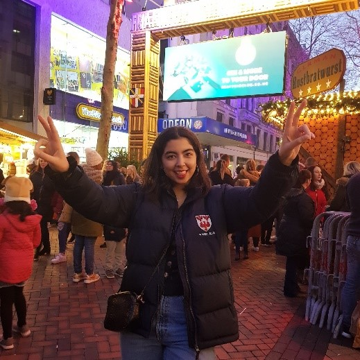 Aqsa standing with her hands up in peace signs and her tongue out. She wears a Queen's College puffer jacket and a crossover bag. She is standing in Birmingham Christmas market. You can see lots of people and stalls behind her, everything is lit up with Christmas lights.