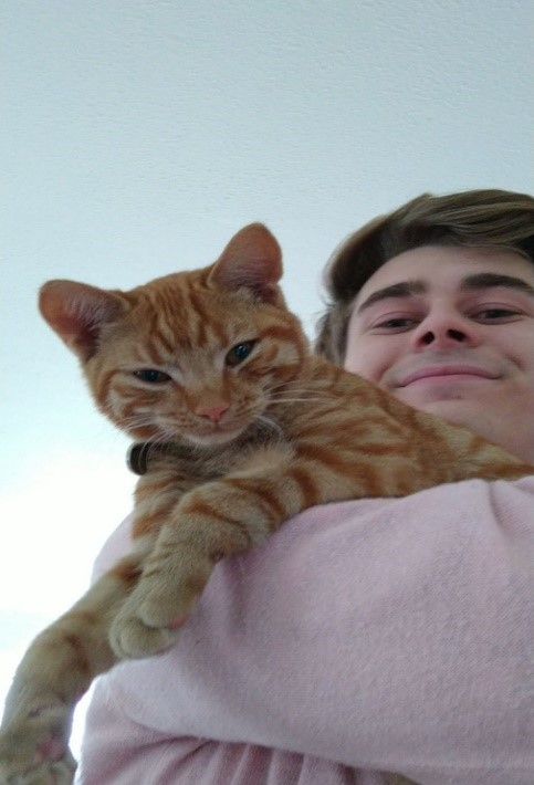 Arthur is smiling down at the camera, holding a white and orange striped cat which is also looking down at the camera.