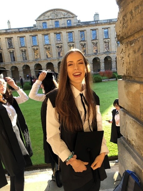 Charlotte dressed in sub fusc, holding her cap, stood smiling in the cloisters of Queen's front quad.