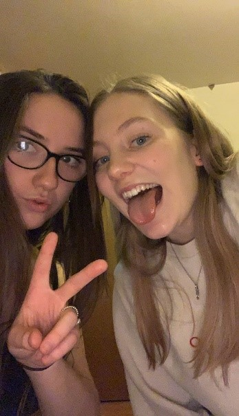 Charlotte (left) and Katie (right) taking a selfie, with Charlotte pouting and doing a peace sign, while Katie sticks her tongue out.