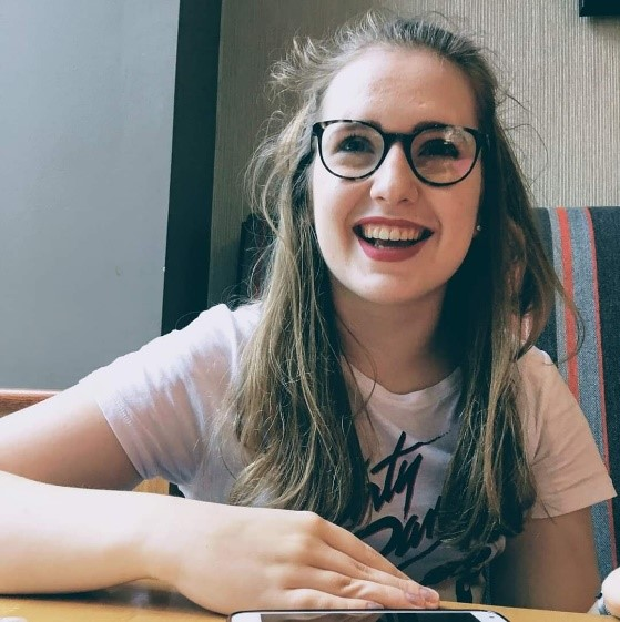 Kyla is sat, leaning on a table, smiling. She is wearing glasses and a white T-shirt with black writing, which is largely covered by her hair.
