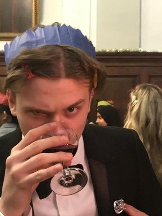 Luke at the Queen's Christmas Dinner, wearing a blue paper hat from a cracker and drinking a glass of red wine, while looking suspiciously at the camera.