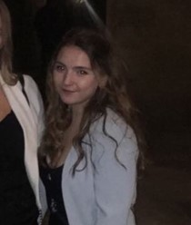 Maddie at a QCBC dinner, wearing a black dress with a white jacket.