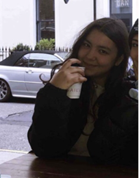 Sophie is smiling at the camera. She is in the right side of the frame and the background is bright behind her. You can see the street with some cars and a white building. She is drinking from a cup.